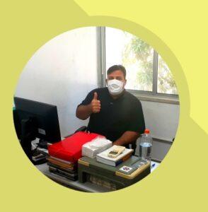 Servidor Rogério Carneiro, do Setor de Educação Continuada/Prex, com máscara facial e fazendo um sinal de positivo na sala onde trabalha